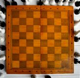 Chess on a chessboard. Old chess around an empty chessboard classic wooden board Royalty Free Stock Photography