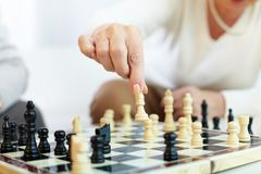 Chess choice. Portrait of senior human hand holding chess figure Stock Images