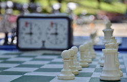 Chess. A close perspective shot of the white pieces on a chessboard backed by a time clock royalty free stock photography