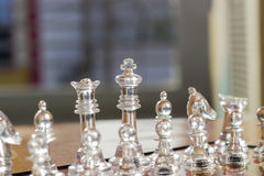 CHESS. A closeup of a chess game with a king piece. Color scheme is white. Use it to represent business strategy, competition or playing a simple game of chess Stock Images