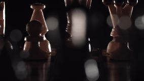 Chess closeup, wooden chess board, business concept, black background. slide camera. Studio. Hand made chess. Dark dramatic backlight stock footage