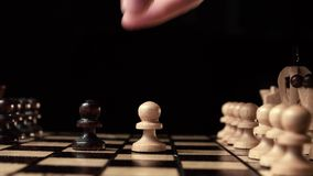 Chess closeup, wooden chess board, business concept, black background. slide camera. Studio. Black chess make the first retaliatory move pawn. chess closeup stock footage