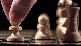 Chess closeup, wooden chess board, business concept, black background. slide camera. Studio. Chess player makes a move the white pawn, a motion Slow chess stock footage