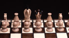 Chess closeup, wooden chess board, business concept, black background. slide camera. Studio. Top view of white chess pieces ready for party. chess closeup stock footage