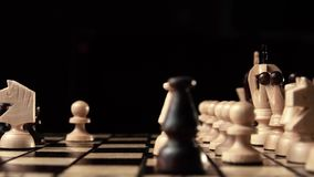 Chess closeup, wooden chess board, business concept, black background. slide camera. Studio. White Chess figure knight in front of black figures. chess closeup stock footage