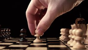 Chess closeup, wooden chess board, business concept, black background. slide camera. Studio. White chess make the first retaliatory move pawn. chess closeup stock footage