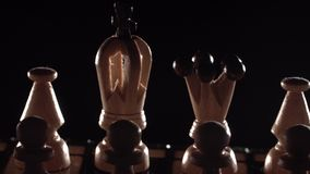 Chess closeup, wooden chess board, business concept, black background. slide camera. Studio. White chess pieces on view through black. chess closeup, wooden stock footage