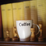 Chess And Coffee. A coffee cup and chess pieces next to some books on a shelf, concept of intelligence. Indoor angled shot Stock Photos