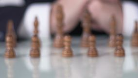 Chess competition, man in suit moving pawn on chessboard, business decision. Stock footage stock footage