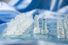 Chess Compromise. Glass chess figures on a chessboard with kings meeting on the battlefield to make an agreement, blue satin background Royalty Free Stock Images