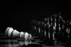 Chess concept. Black chess army defeats white king on the chess board Royalty Free Stock Images