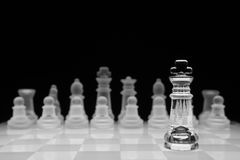 Chess concept,  on black. Glass king chess piece against other team. Black and white, shallow depth of field Stock Photography