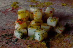 Cheese cubes with various spices Stock Image