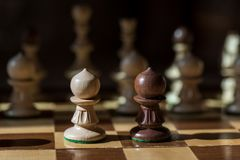 Chess face off one on one. Two pawns face off on a chess board with other pieces in the background Stock Image