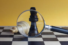 Chess fight concept with two chess kings and magnifying glass. Stock Photo