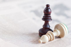 Chess figure on newspaper, business concept - strategy, leadership, team and success, man and woman in business. Good and evil Royalty Free Stock Image