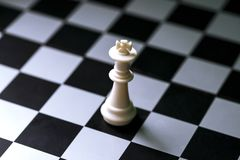 Chess figure white king on chess board. Chess game. Checkered board. White king alone on chessboard. Mate situation in chess rules. Business advantage or Stock Images