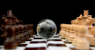 Chess figures against earth globe. Chess figures against  glass globe . Competition  or success  concept Royalty Free Stock Photo