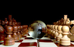 Chess figures against earth globe. Chess figures against  glass globe . Competition  or success  concept Stock Photo