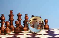 Chess figures against earth globe. Chess figures against  glass globe . Competition  or success  concept Stock Image
