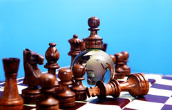 Chess figures against earth globe. Chess pawn on glass globe . Winner or success  concept Royalty Free Stock Photography