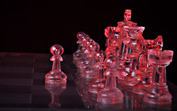 Chess figures on a board. Translucent red glass chess figures on a board Stock Photo