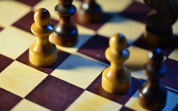 Chess figures on a chessboard Stock Images