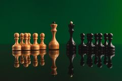 Chess figures on green background with reflection. Chess pawns with queen leaders on green background with reflection. Confrontation of rival pieces for Royalty Free Stock Photography