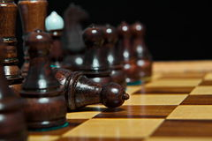 Chess figures on old wooden table. Checkmate Royalty Free Stock Image