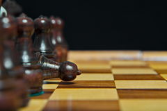 Chess figures on old wooden table. Checkmate Stock Photo