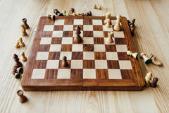 Chess figures scattered on chessboard at the table Royalty Free Stock Photos