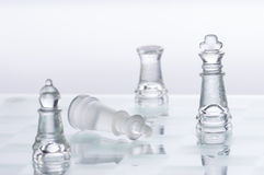 Chess Figures. Transparent chess figures, on reflective chess board with white background, with one king down representing defeat stock image