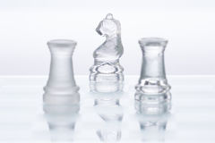 Chess Figures. Transparent chess figures, on reflective chess board with white background, two rooks on opposing sides stock photography