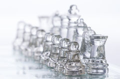 Chess Figures. Transparent chess figures, on starting position, on reflective chess board with white background stock photo