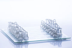 Chess Figures. Transparent chess figures, on starting position, on reflective chess board with white background stock photography