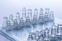 Chess Figures. Transparent chess figures, on starting position, on reflective chess board with white background royalty free stock photo