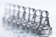 Chess Figures. Transparent chess figures, on starting position, on reflective chess board with white background, with focus on pawns stock photo