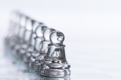 Chess Figures. Transparent chess figures, on starting position, on reflective chess board with white background, with focus on pawns royalty free stock image