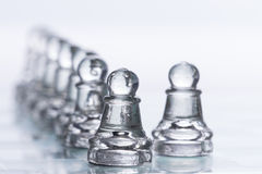 Chess Figures. Transparent chess figures, on starting position, on reflective chess board with white background, with focus on pawns stock photos