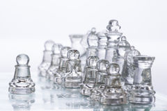 Chess Figures. Transparent chess figures, on starting position, on reflective chess board with white background, with one pawn in front, leading royalty free stock images