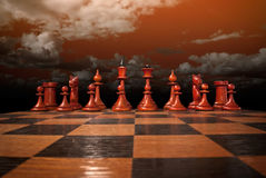Chess figures under a red sk Royalty Free Stock Images