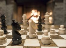 Chess by the fireplace Royalty Free Stock Photo