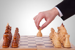 Chess. The first step. Hand chess and a chess board with chess pieces Stock Images