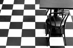 Chess floor with black table and chair, creating  an interesting background Stock Images
