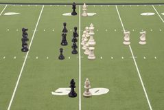 Chess Football 50 Yard Line Play. Chess pieces lined up as football teams Stock Images