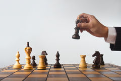 Chess game. Wooden chess and hand holding the queen Stock Images
