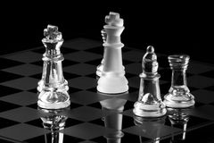 Chess game. Frosted glass King chess piece surrounded by regular glass chess pieces Stock Images