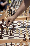 Chess game. A hand moving chess figure in a chess game Royalty Free Stock Photos