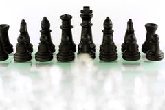 Chess game. In front of white background, focused on black figures Royalty Free Stock Images