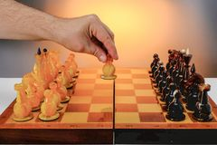 Chess game with amber chess pieces on the board. First move, hand of player holding white figure. With gradient gold background stock photos